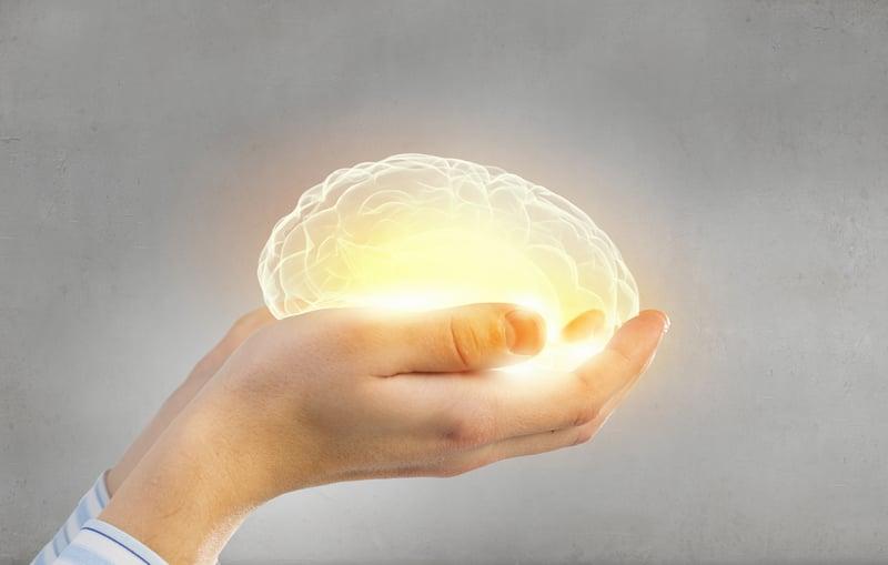 hands holding luminated brain